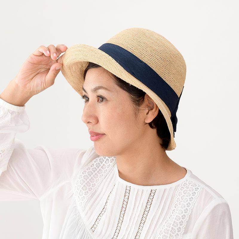 田中帽子店 uk-h090 Nadia ナディア ラフィア 綿麻リボン 女優帽 57.5cm 綿麻のリボンが爽やかな印象のラフィア帽子 マダガスカル原産の天然素材ラフィア。柔らかいのが特長です。そのラフィアを手編みし、たためる女優帽を作りました。リボンには夏らしい綿麻素材を使用。大きなリボンがデザインのアクセント。色は、しまった印象のネイビーと優しいトーンのカーキの2色。