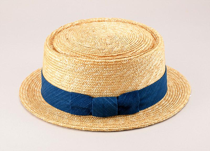 田中帽子店 小島屋 uk-kh036 藍染 ポークパイハット 95cm 7本の麦を紐状に編み上げた麦わら真田が材料  麦わら帽子に使われるのは主に大麦の茎。それを7本組み、真田ひも状に編んだ「麦わら真田」が材料となります。1本1本手で編み上げられた真田を霧吹きで湿らして縫製し、型入れして天日で水分を飛ばした後、乾燥させて装飾します。この縫製→型入れ→装飾という流れを3人で分業して進めていくことで、1つの帽子が仕上がります。